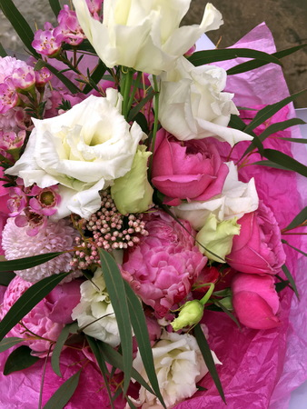 Close up of bouquet of fresh flowers on a light background. Pink roses, white eustoma, pink roses and pink Chamelaucium in a bouquet of fresh flowers on a light background.