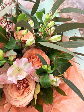 Close-up Beautiful Bouquet. Bouquet of flowers orange rose, white Eustoma. Beautiful bright flowers background. Beige bouquet