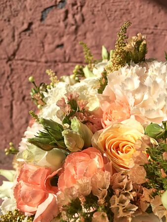 Bouquet for bride isolated on background. Bridal beautiful bouquet made of different flowers orange and white roses, chamelaucium, dianthus, eustoma on background. 写真素材