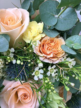 Bouquet printanier de fleurs aux couleurs vives. Bouquet de fleurs comprenant eryngium bleu, lisianthus jaune, roses oranges, hamelacum, eucaliptus. Fond de belles fleurs lumineuses.