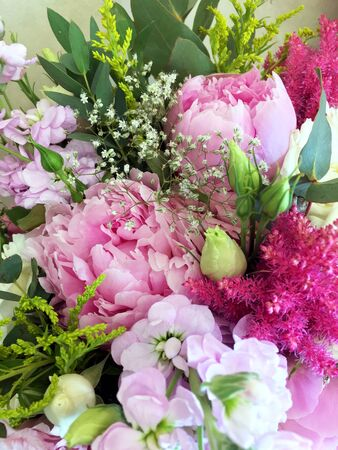 Peony flowers with pink and white petals in a bouquet. Pink bouquet with peonies and white roses.