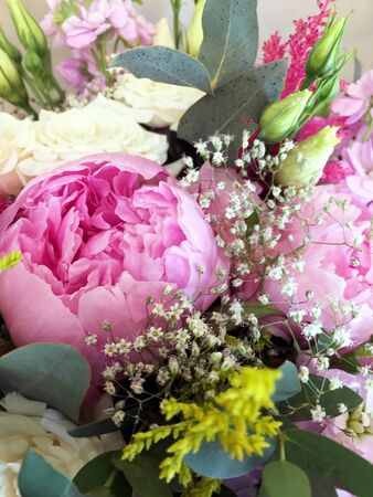 Pink bouquet with peonies and pink and white roses. A bouquet of beautiful luxury flowers, close-up.