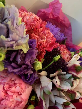 Bouquet of mixed colorful flowers. Flowers bouquet including artishock, pink dianthus, alstroemeria, peony and eustoma. Beautiful bright flowers background.