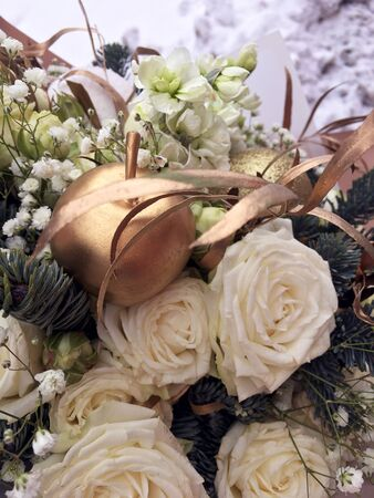 Christmas golden bouquet. Winter bouquet of fresh Nobilis, gold apple, white roses, white ball. A bouquet of fresh nobilis, gold leaf, fir branches, cones and gold apple. Banco de Imagens