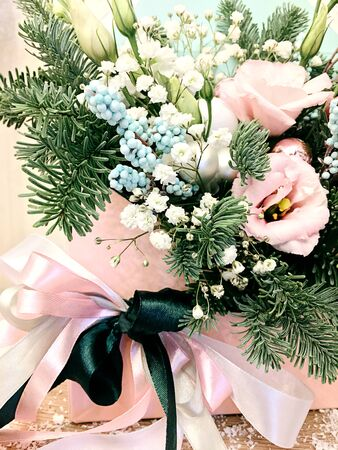 Winter decor. The composition of fresh Nobilis, of fresh Nobilis, pink flowers ,decorative berries, pink ribbon in a box.