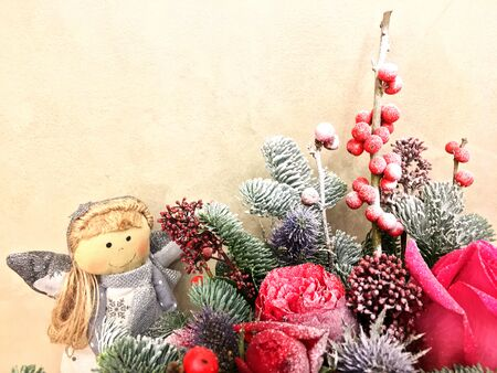 Beautiful Christmas decoration background. Christmas winter composition whit Fir cone, red roses and berries with snow. Christmas decoration background.