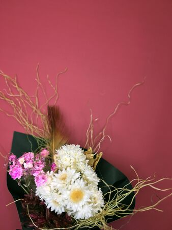 Beautiful dry flower bouquet on red background.