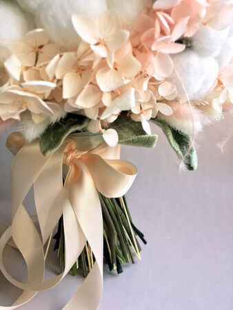 Flower arrangement cotton blooms in white, roses in a beautiful blend of peach, light peach and white color, preserved hydrange. Preserved flower bouquet close up.