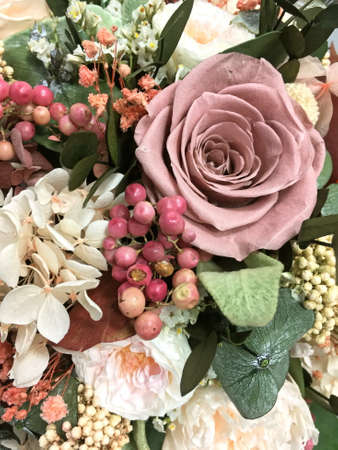 Long lasting flowers decoration. Preserved roses with dried flowers and green leave bouquet closeup.