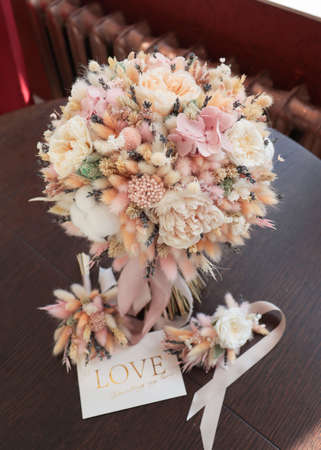 Stylish bridal bouquet of preserved flowers and lagurus with boutonniere. Dried and preserved flowers brides bouquet in delicate peach tones from cotton,roses and lagurus.