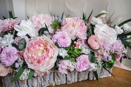 Gift basket with beautiful flowers. Bouquet of white and pink flowers. Preserved flowers.