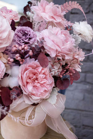 Bouquet with roses and dry flowers in pink colors. Stabilized flowers in a white beige box. Interior decor.