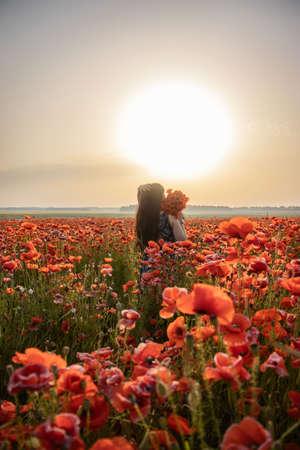 Girl in a poppy field. A girl stands in a flower garden. A woman walks in a meadow with beautiful red flowers.