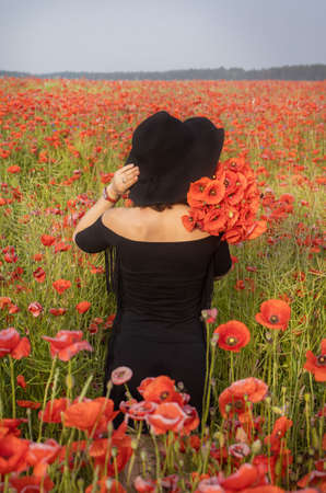 Girl with black hat in a poppy field. A womanstands in a flower garden. A girl walks in a meadow with beautiful red flowers. Stockfoto