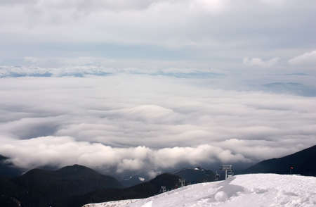 pista: Ski lift in clouds with forest and snow