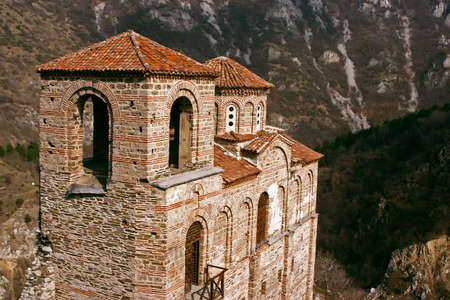 Old antique ortodox church in mountains with trees Stock Photo
