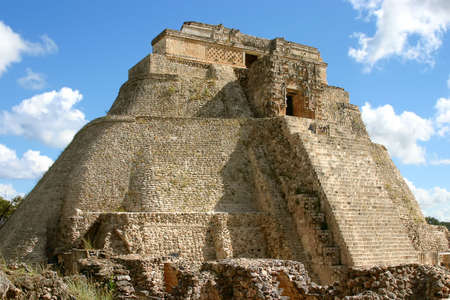 Uxmal main pyramid over blue sky with clouds