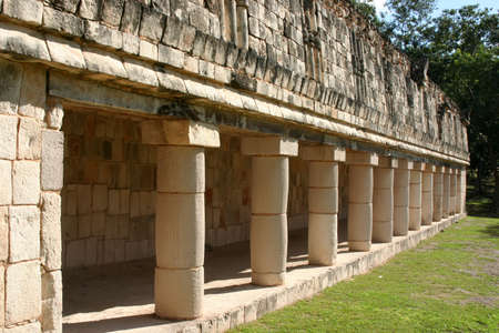 Row of antique maya columns with green grass photo