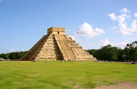 Antique mayan pyramid on green field over blue sky photo