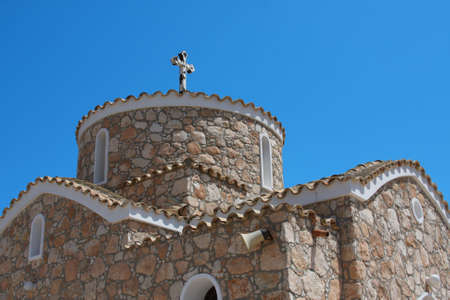 Greek church with cross over blue sky