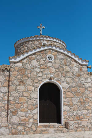Greek church with cros over blue sky