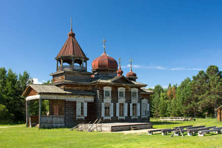 Antique old russian wooden church in the green forest photo