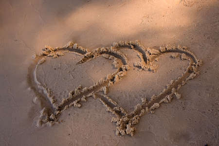 Double hearts painted on the yellow sand