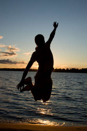 Young man jump over sunlight near the river