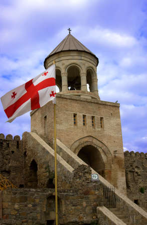 Georgian national red flag over orthodox church and blue sky Stock Photo