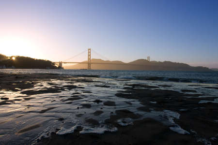 Golden Gate at the dusk with water on sand