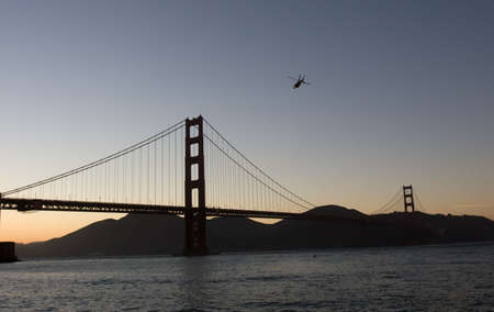 Helicopter over Golden Gate bridge at the dusk Stock Photo