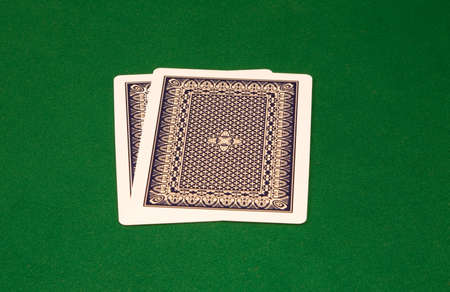 Two cards with faces down on the green table