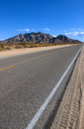Old asphalt road in the California with blue sky