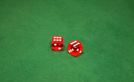 Two red dices on the green table in casino Stock Photo