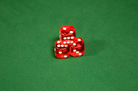 Three red dices on the green casino table