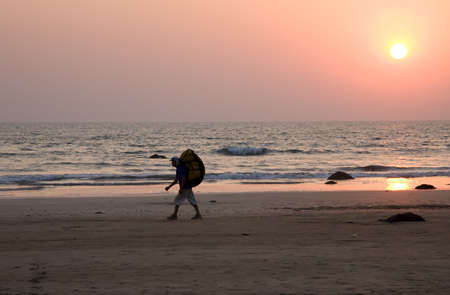 Sunset on the beach with tourist with big backpack Stock Photo