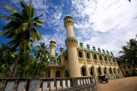 Antique islamic mosque in the green palms on the beach