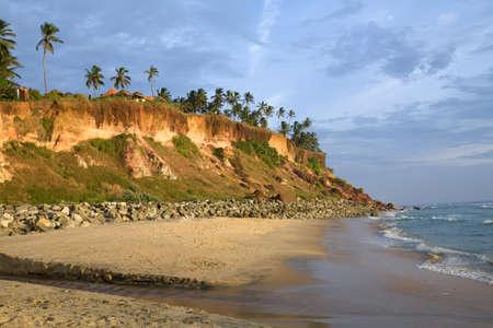Cliffs on the beach near the ocean over blue sky Stock Photo