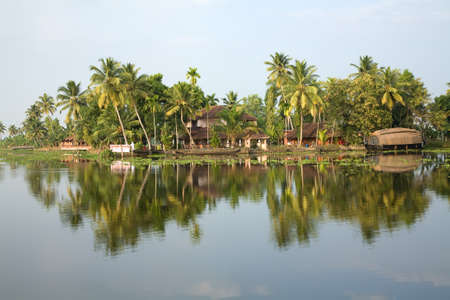 Reflection in river water of tropic palms and houseboat