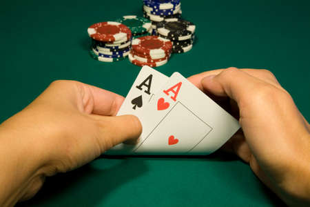 Two aces in hand in game poker on the green casino table Stock Photo