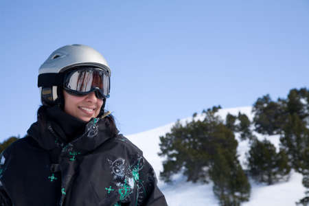 Pretty gorl in snowboard clothes in helmet over blue sky Stock Photo