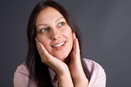 Smiling woman closeup portrait over gray in studio