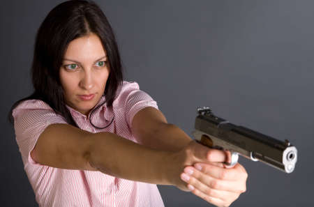 Pretty caucasian girl with gun aiming to somebody over gray