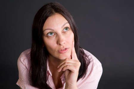 Pretty caucasian girl thinking over gray in studio Stock Photo