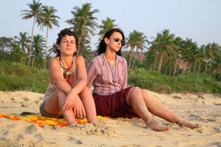 Two pretty girls sitting on the beach sand over sunset in Goa