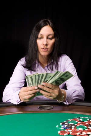 Pretty caucasian girl in the casino takes cash over green felt Stock Photo