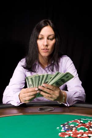 Pretty caucasian girl in the casino takes cash over green felt Stock Photo