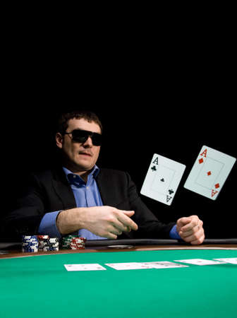 Stylish man in black suit folds two aces in casino poker at Las Vegas