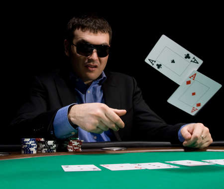 Stylish man in black suit folds two aces in casino poker at Las Vegas over black photo