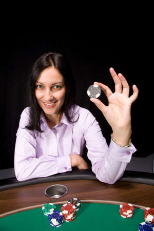 Pretty caucasian girl holds casino chip in hand over black Stock Photo